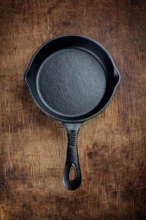 Vintage cast iron skillet  on rustic wood background. Archivio Fotografico