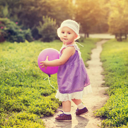 Little girl with a purple balloon photo