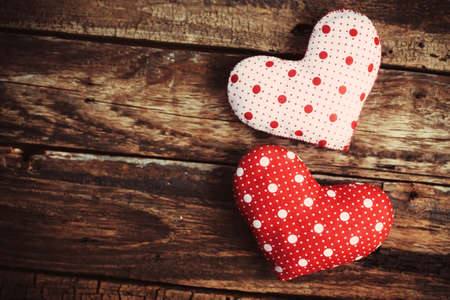Two hearts made of cloth on a wooden surface