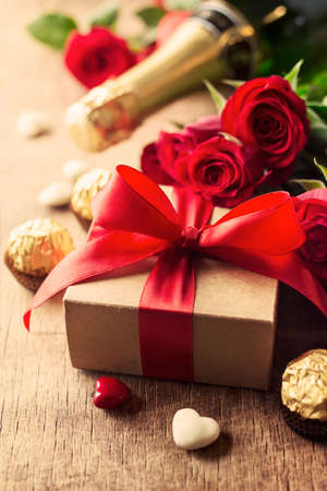 Gift with red bow and heart-shaped candles on the wooden background photo