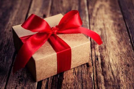 Caja de regalo con una cinta roja sobre un fondo de madera