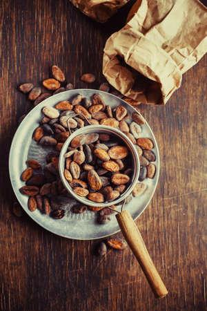 Granos de cacao en el cazo sobre una superficie de madera Foto de archivo