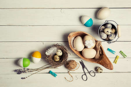 colorful easter eggs and decorations on white wooden table