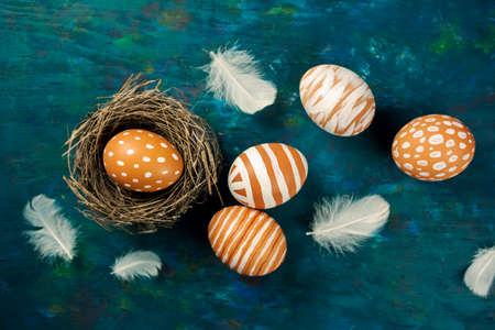 Easter eggs in the nest on rustic blue background photo
