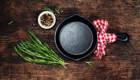 料理の食材と空の鋳鉄製フライパン