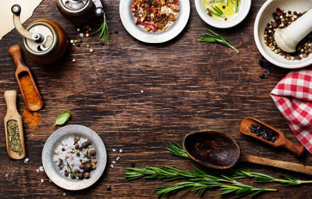 Spices for use as cooking ingredients on a wooden background, with copyspace
