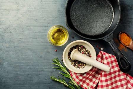 utensilios de cocina: fondo de alimentos con hierro fundido sartén, las hierbas y las especias de selección Foto de archivo