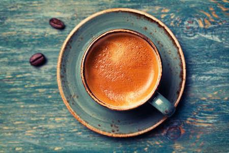 Espresso en una taza azul sobre un fondo de madera