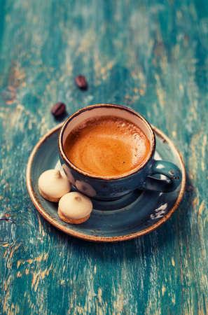 青いテーブルの上のクッキーとコーヒーのカップ