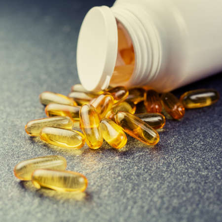 fish oil: fish oil pills oil capsules spilling out of a bottle