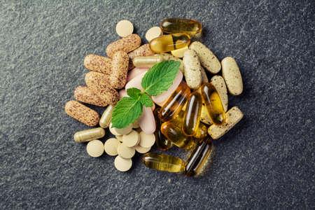 vitamina a: p�ldoras y multivitaminas en un fondo negro Foto de archivo