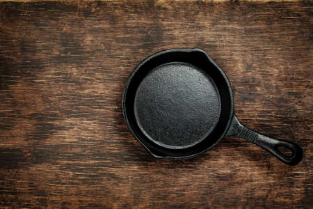 Vintage cast iron skillet on rustic wood background. Stock Photo