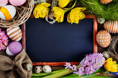 Black board on wooden table, Colorful Easter Eggs and flowers