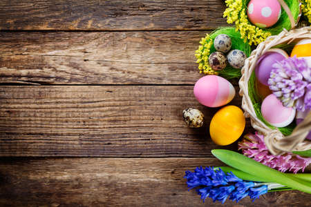 Easter decorations  on wooden table, colored eggs and flowers. Top view