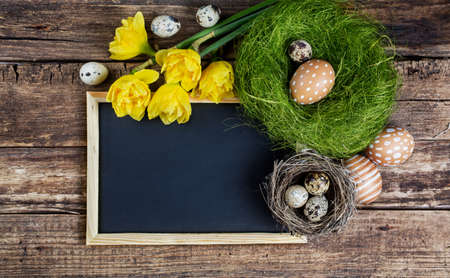 Easter decorations and black board with copy space on wooden background. Standard-Bild