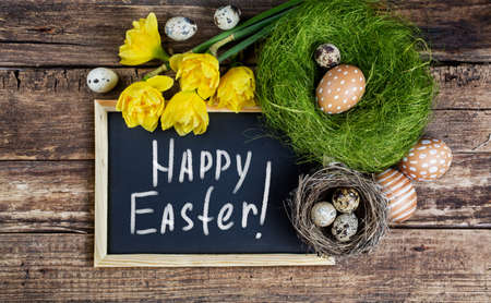 easter nest: Easter Eggs and black board with text - Happy Easter. Stock Photo