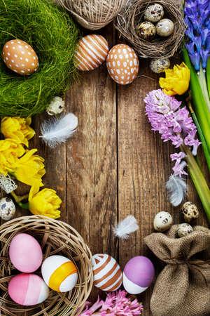 오래 된 나무 테이블에 깃털과 다채로운 부활절 달걀 스톡 콘텐츠