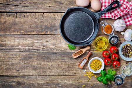 jídlo: Ingredience pro vaření a litinový pánev na starý dřevěný stůl. Potraviny pozadí koncept s copyspace
