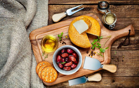 cheese platter: Cheese, olives and olive oil on board, top view Stock Photo