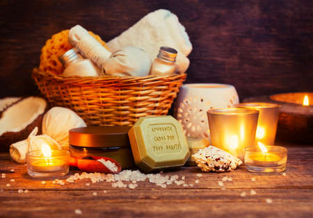 CPA still life, olive oil soap, candles, sea salt and body cream on wooden table photo