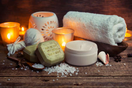 body oil: Body lotion, soap and towel on a wooden surface, Spa still life