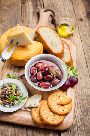 Greek olives and cheese on a wooden board photo