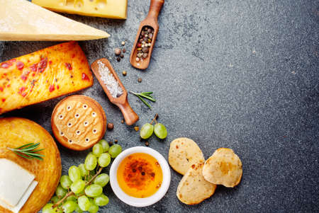 crackers: Various types of cheese with snack, grapes and crackers
