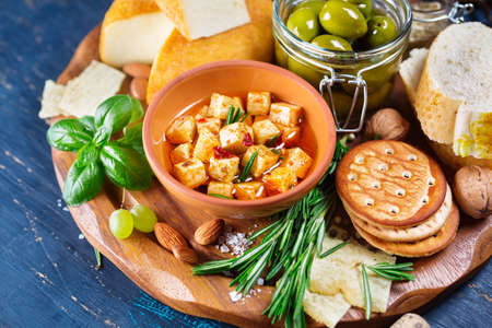 appetiser: Cheese with olives and green herbs, party snack appetiser Stock Photo
