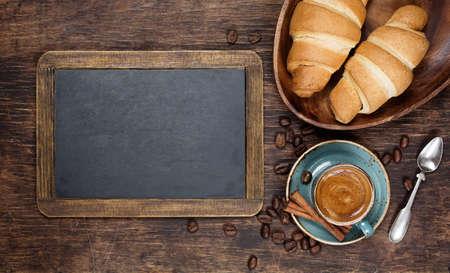 pasteleria francesa: Croissants y caf� con pizarra de la vendimia con copyspace Foto de archivo