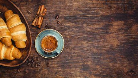 クロワッサン、素朴な暗い背景にコーヒー。Copyspace と食品の背景