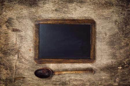 recipe background: Wooden spoon and Blackboard on a rustic dark background