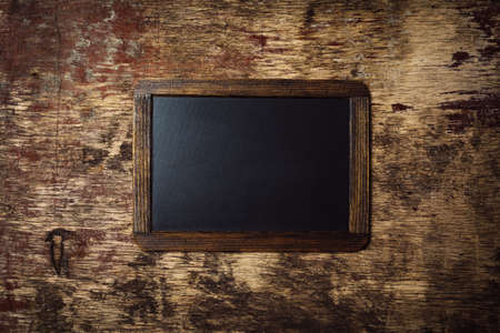 small wooden framed blank chalkboard on a old dark background photo