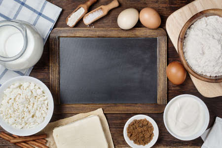 cakes and pastries: Traditional baking ingredients with vintage chalkboard. Rustic background with free text space. Stock Photo