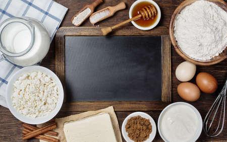 Ingrediënten voor het bakken - melk, eieren, meel, kwark, boter, suiker, zure room. Rustieke achtergrond met vintage schoolbord met copyspace Stockfoto
