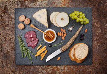 jamon y queso: Antipasto mixto: Queso y uvas, miel, nueces, peras sobre un fondo oscuro rústico Foto de archivo