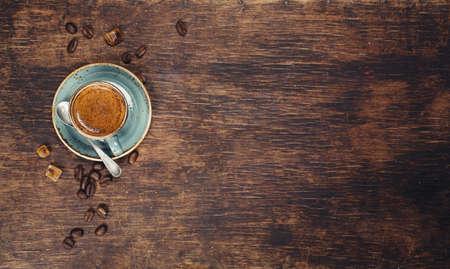 trompo de madera: Espresso en un cuenco azul sobre un fondo de madera