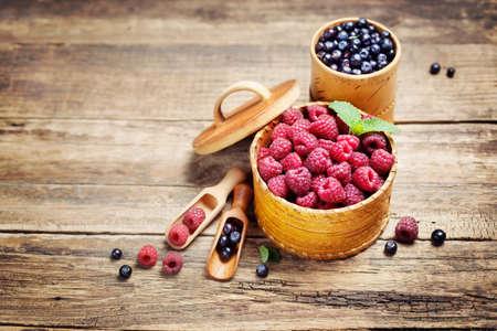 comida gourmet: Frambuesas y arándanos en un tazón en el fondo de madera rústica. Alimentación de fondo, copyspace
