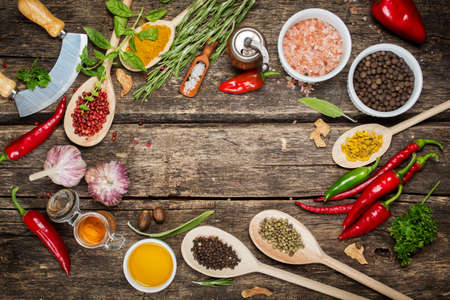 seasonings: Various spices and herbs with copyspace, pink pepper, Himalayan salt, garlic and olive oil Stock Photo