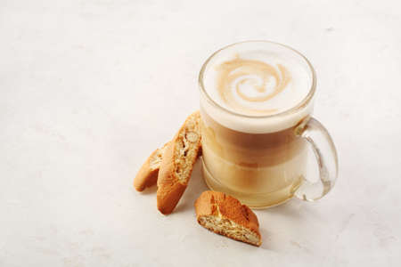 cappuccino: Cappuccino with biscotti or cantucci on a white table. Food background with copyspace Foto de archivo