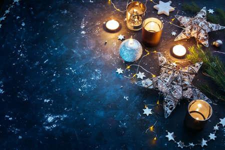 De achtergrond van Kerstmis met feestelijke decoratie, sterren en kaarsen. Kerst achtergrond met copyspace