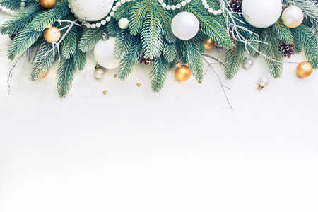 christmas decorations with white background: Christmas Tree Pine Branches and Christmas balls on a light background.