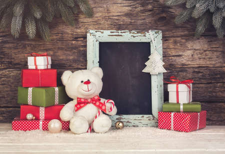christmas tree branch: Merry Christmas still life with Teddy Bear and gift boxes and  Chalkboard  with copyspace Stock Photo