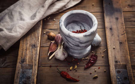 condiments: Condiments and Mortar  on a old rustic table Stock Photo