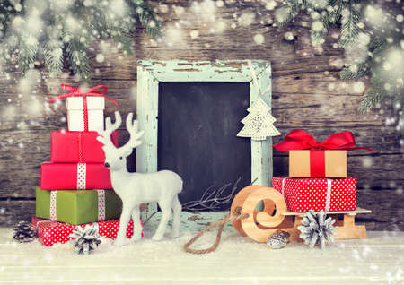 Christmas background with gift boxes and festive decoration. Vintage blackboard with copyspace.