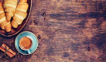 Cup of coffee and croissant with coffee bean on wooden table