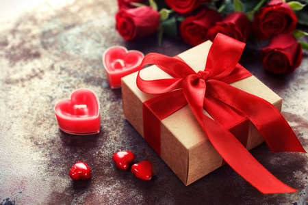 red gift box: Valentines Day, Gift box of kraft paper with a red ribbon and  candles. Rustic style