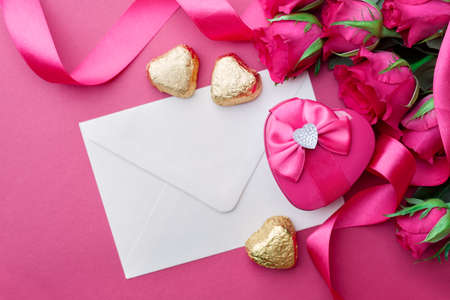 curved ribbon: Heart shaped Valentines Day gift box with curved ribbon and envelope on pink background.