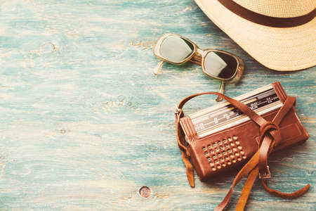 Old retro sunglasses, radio and a hat on a wooden table
