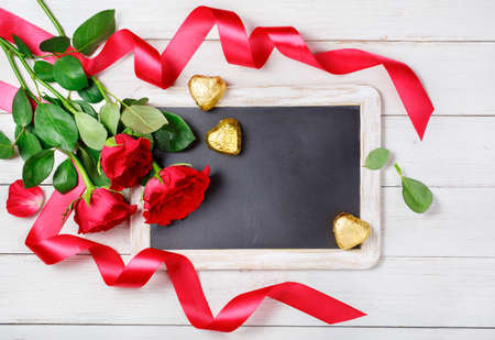 romantic love: Red roses, candy and blackboard with copyspace. Valentines Day background