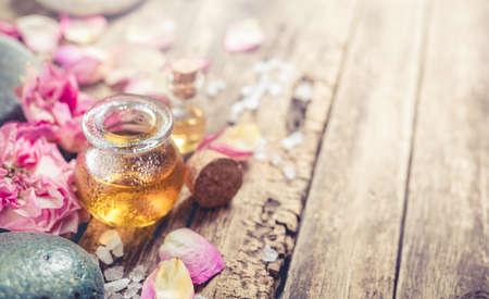 Massageöl, Blütenblätter Blumen und Zen-Steine. SPA Hintergrund in einem rustikalen Stil mit Exemplar. Shallow DOF